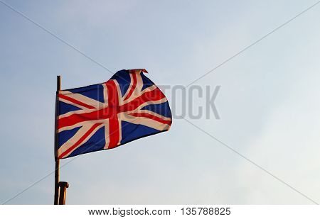 united kingdom or Britain flag on blue sky with wood pole