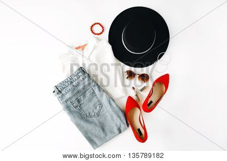 flat lay feminini clothes and accessories collage with blouse jeans sunglasses bracelet lipstick red high heel shoes earrings and hat on white background.