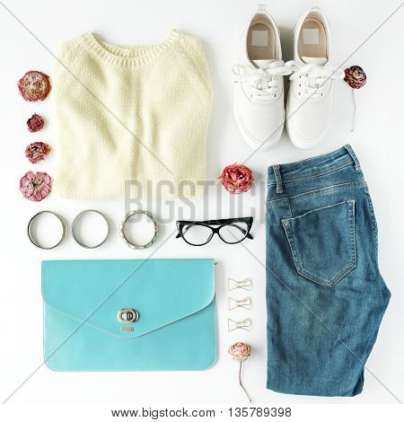 flat lay feminine clothes and accessories collage with cardigan jeans glasses bracelet clutch shoes and dry roses on white background.