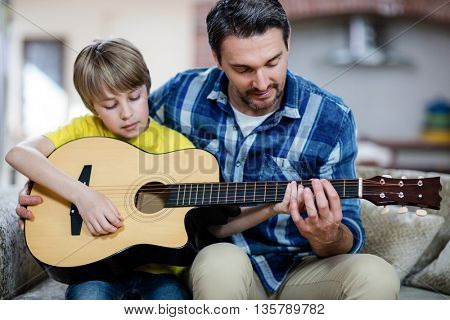 Father and son playing a guitar at home