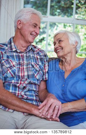 Smiling senior couple holding hands while sitting on sofa at home