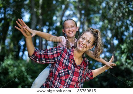 Portrait of playful mother and daughter in back yard