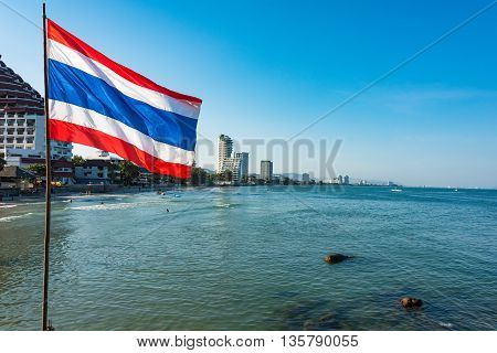Thailand flag with sea and skyscrapers of Hua Hin city on the background