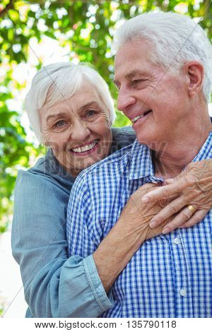 Cheerful retired couple hugging while standing outdoors