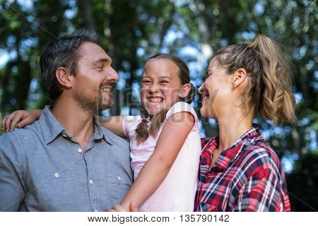 Laughing daughter with parents in back yard