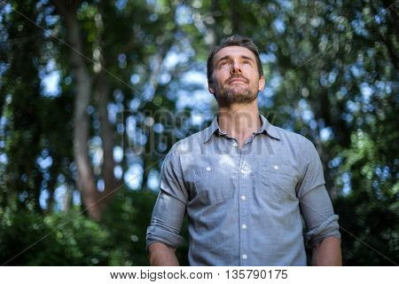 Young man day dreaming while standing in back yard