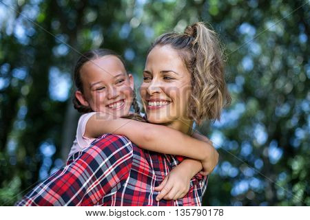 Laughing mother carrying daughter while looking at her in back yard
