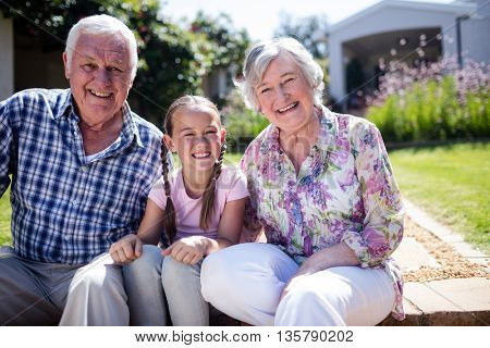 Grandparents and granddaughter sitting in the garden on a sunny day