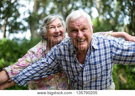 Senior couple with arms outstretched looking up in back yard