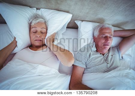 Irritated senior woman blocking ears with pillow while husband snoring on bed