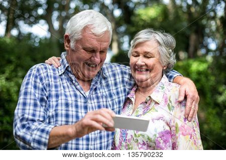 Happy senior couple holding smart phone standing in back yard