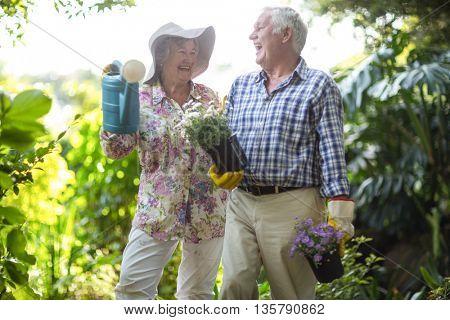 Senior couple laughing while holding gardening equipment