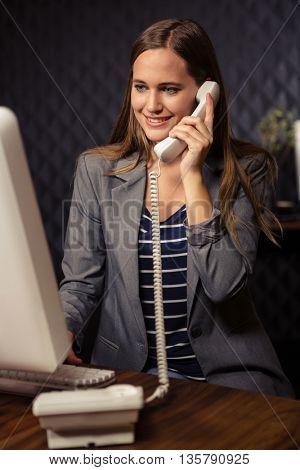 Creative businesswoman land line in office