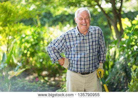 Portrait of senior man standing with equipment in garden