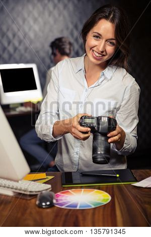 Creative businesswoman looking at pictures on camera in office