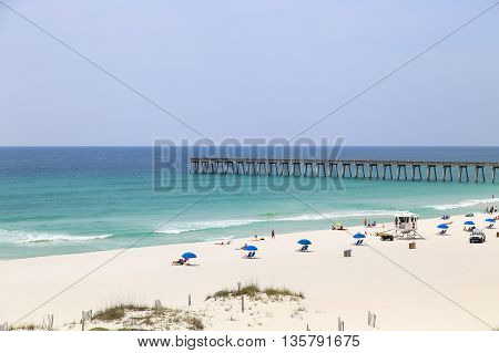 PENSACOLA BEACH, USA - MAY 13, 2015: People relaxing and sunbathing on the beach with beach chairs and sunshades. In the back the Pensacola Beach Gulf Pier.