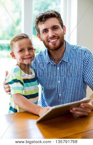 Portrait of smiling father and son with digital tablet at home