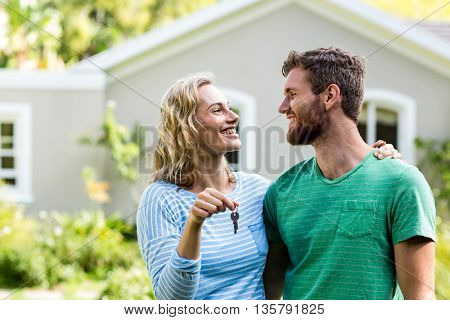 Smiling couple looking eachother while holding keys against house