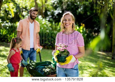Smiling woman holding flower pot with family in background at yard