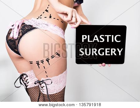 young woman in lacy lingerie, holding a tablet pc with plastic surgery sign. Drawing lines on a Caucasian woman's ass as marks for ass cellulite cosmetic correction surgery.