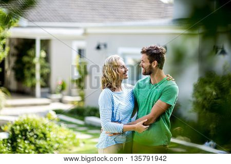 Smiling couple embracing against house