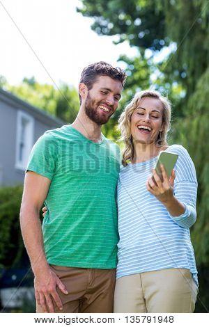 Happy couple taking selfie in yard