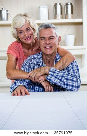Portrait of happy senior couple hugging in kitchen at home