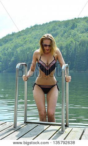 Pretty young sexy woman in bikini posing outdoor in summer