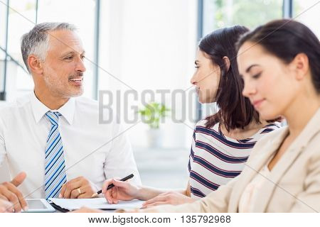 Businesspeople discussing at desk in the office