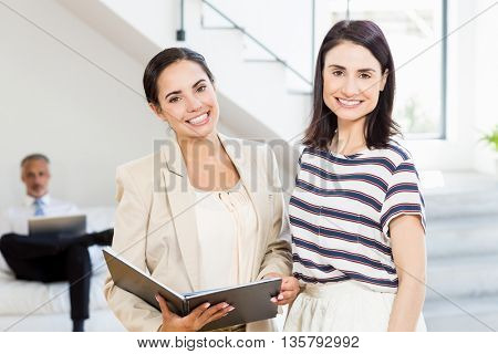 Portrait of businesswoman and a colleague holding diary in the office
