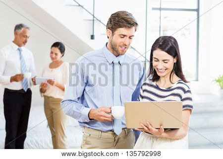 Businessman holding coffee cup and a colleague using laptop in the office