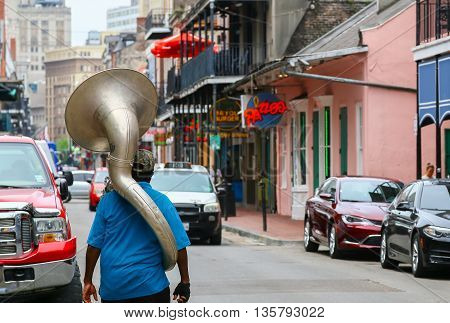 NEW ORLEANS, USA - MAY 14, 2015: A man with a sousaphone on his back walking down Bourbon Street in French Quarter.