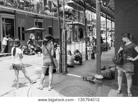 NEW ORLEANS, USA - MAY 14, 2015: Scene from Royal Street in French Quarter with a band playing live music on the street and several people gathered around it. The picture is monochrome.