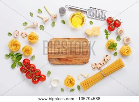 Fettuccine and spaghetti with ingredients for cooking pasta on a white background with blank of wooden kitchen board top view. Flat lay