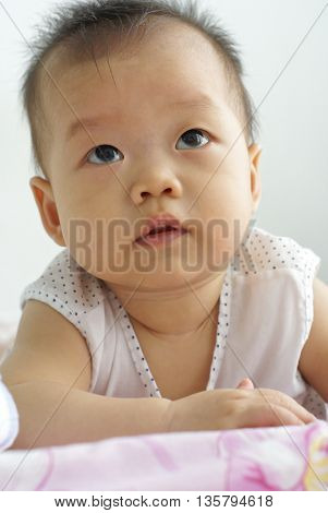 Cute baby looking for something In front of her. Face of cute Asian infant looking to someone.