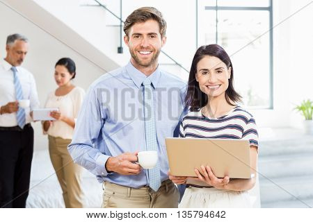 Portrait of businessman holding coffee cup and a colleague holding laptop in the office