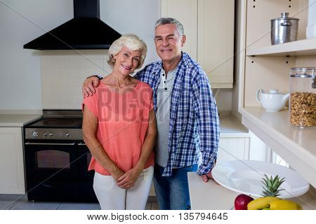 Portrait of smiling senior man with woman standing in kitchen at home