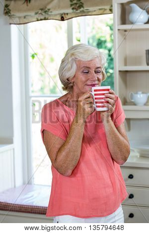 Happy senior woman having coffee in kitchen at home