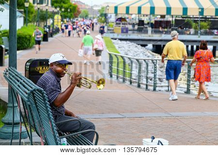 NEW ORLEANS, USA - MAY 14, 2015: Trumpeter sitting on a bench on the Riverwalk with many people walking by.