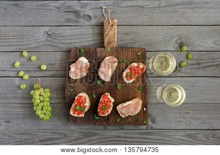 Wine with appetizers for wine and grapes. Sandwich with tomatoes goat cheese and ham on a wooden board on a wooden table. Rustic style top view