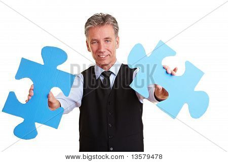 Senior Manager Holding Jigsaw Pieces
