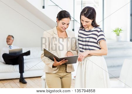 Businesswoman and a colleague looking at diary in the office