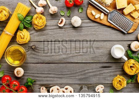Frame with spaghetti and fettuccine with various ingredients for cooking pasta on a wooden table top view. Flat lay