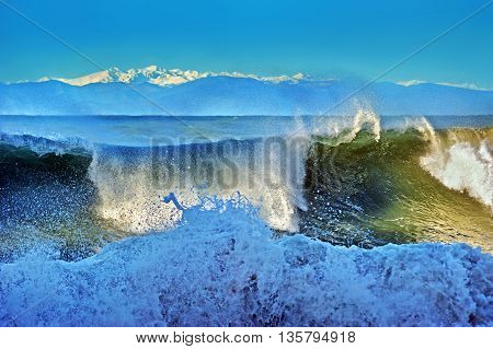 powerful stormy waves and snow-capped mountains background