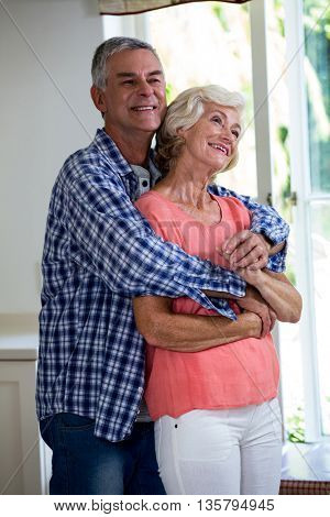 Romantic smiling couple embracing in kitchen at home