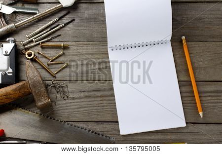 vintage tools with a notebook with blank pages on wooden table in the workshop top view