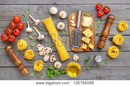 Spaghetti and fettuccine with different ingredients for cooking pasta on a wooden table top view. Flat lay