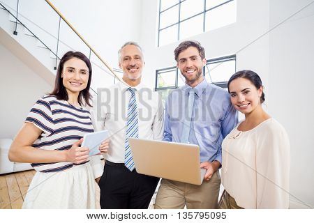Portrait of Business people holding digital tablet and laptop in the office