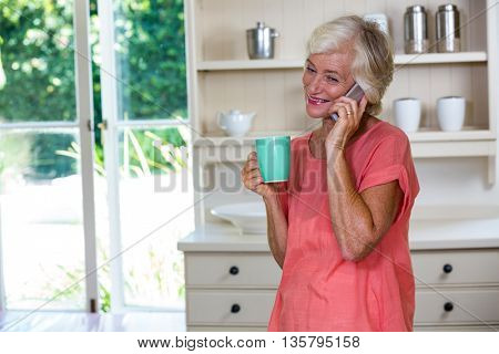 Happy senior woman talking on phone while having coffee in kitchen at home