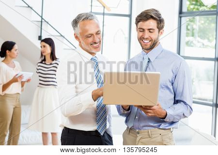 Businessmen interacting using laptop in the office